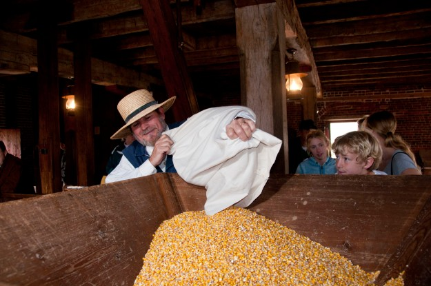 The miller pours corn into the hopper to be ground.