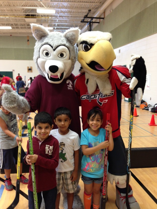 Buddy the Wolf enjoys playing street hockey with Washington Capitals' mascot Slapshot.