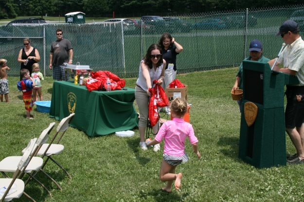 Summer intern Kathryn Wagner hands out goodie bags during a ceremony marking the start of the Water Mine expansion project at Lake Fairfax Park.