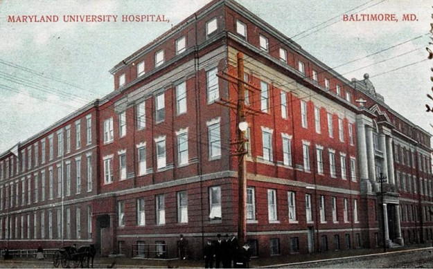 A postcard photo of the Maryland University Hospital, where Elizabeth Collins Lee received her nursing training. It is postmarked from Baltimore, MD on Oct. 6, 1909. The postcard shows details such as utility lines, the tracks on the street, and people in period clothing.