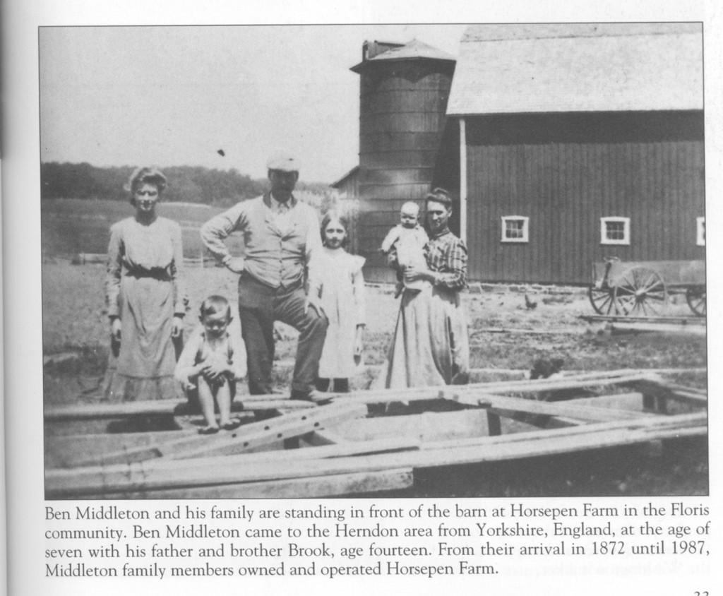 a newspaper clipping of Ben Middleton and his family with text below that reads: Ben Middleton and his family are standing in front of the barn at Horsepen Farm in the Floris community. Ben Middleton came to the Herndon area from Yorkshire, England, at the age of seven with his father and brother Brook, age fourteen. From their arrival in 1872 until 1987, Middleton family members owned and operated Horsepen Farm.
