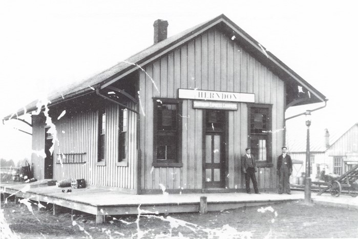 a black and white, worn photo of the Herndon train station