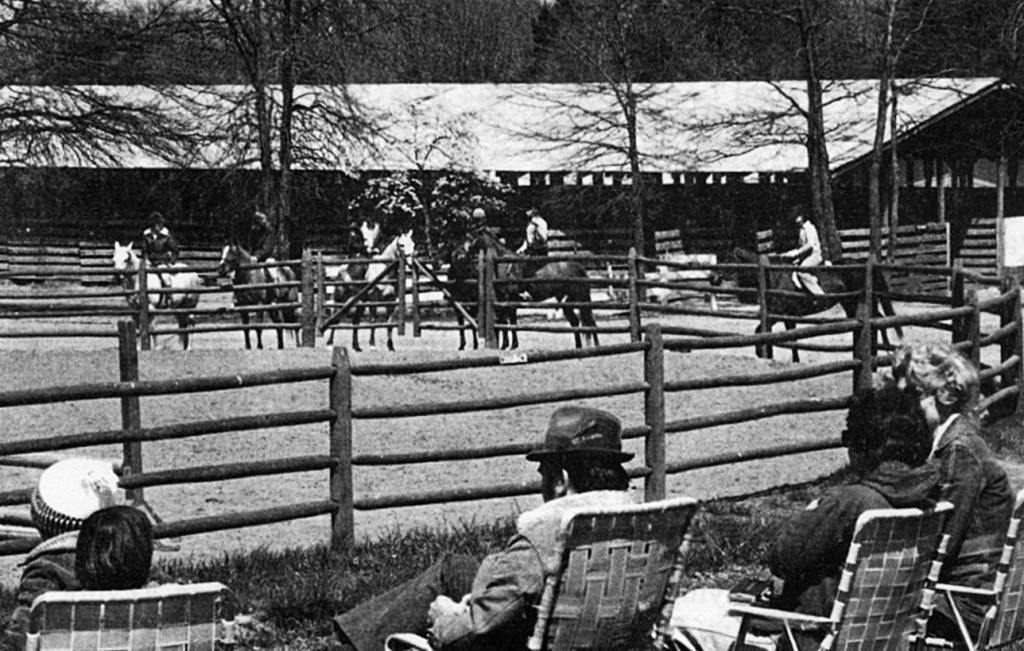 an old black and white photo of people watching a horse show