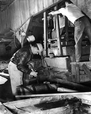 an old black and white photo of two people working to make apple cider