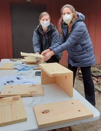 two people making squirrel boxes